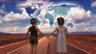 boy and girl holding hands looking down road and sky with may of world in clouds