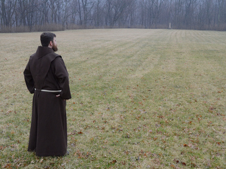 friar looking across field to St. Anthony Statue