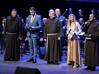friars and orchestra on stage