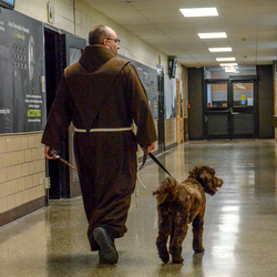 Friar and dog in school