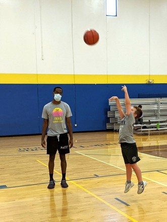 boy throwing basketball with instructor