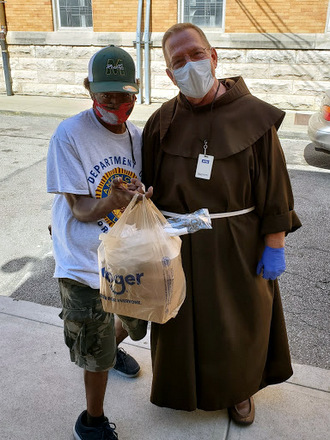 friar giving bag of food to client