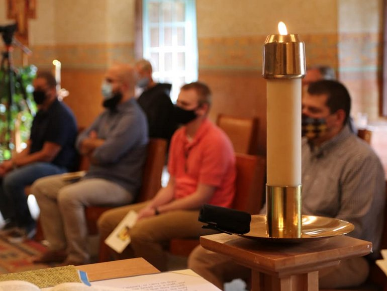 novices in masks in background with candle in foreground