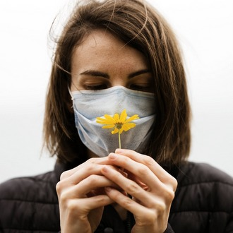 woman in mask holding flower