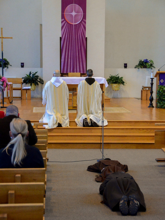friars kneeling at altar and friars lying prostrate