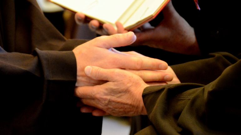 friar hands clasping
