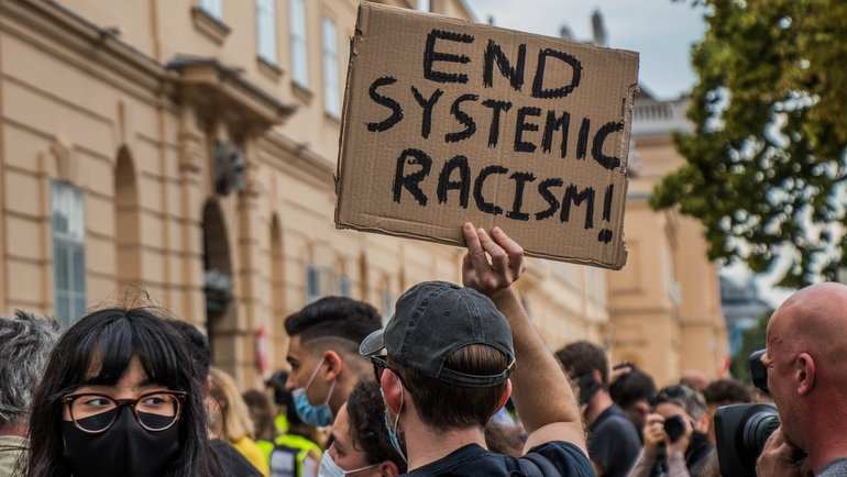 Racism poster and protesters