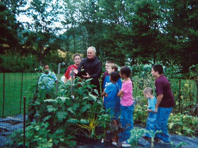 friar in garden with students