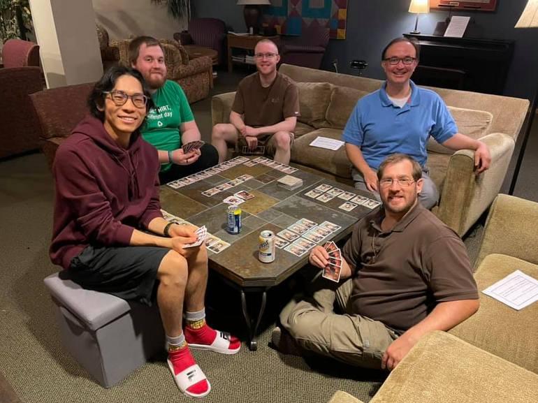 5 men sitting around table playing card game