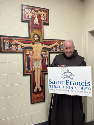 friar with sign and San Damiano Cross